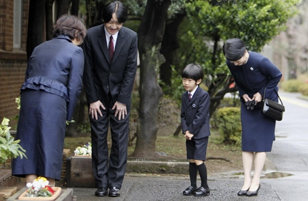 Japan's Prince Hisahito (2nd R), accompanied by his father Prince Akishino (2nd L) and mother Princess Kiko (R), is greeted upon arrival at Ochanomizu University's affiliated kindergarten for his graduation ceremony in Tokyo March 14, 2013.   REUTERS/Junji Kurokawa/Pool (JAPAN - Tags: ROYALS)