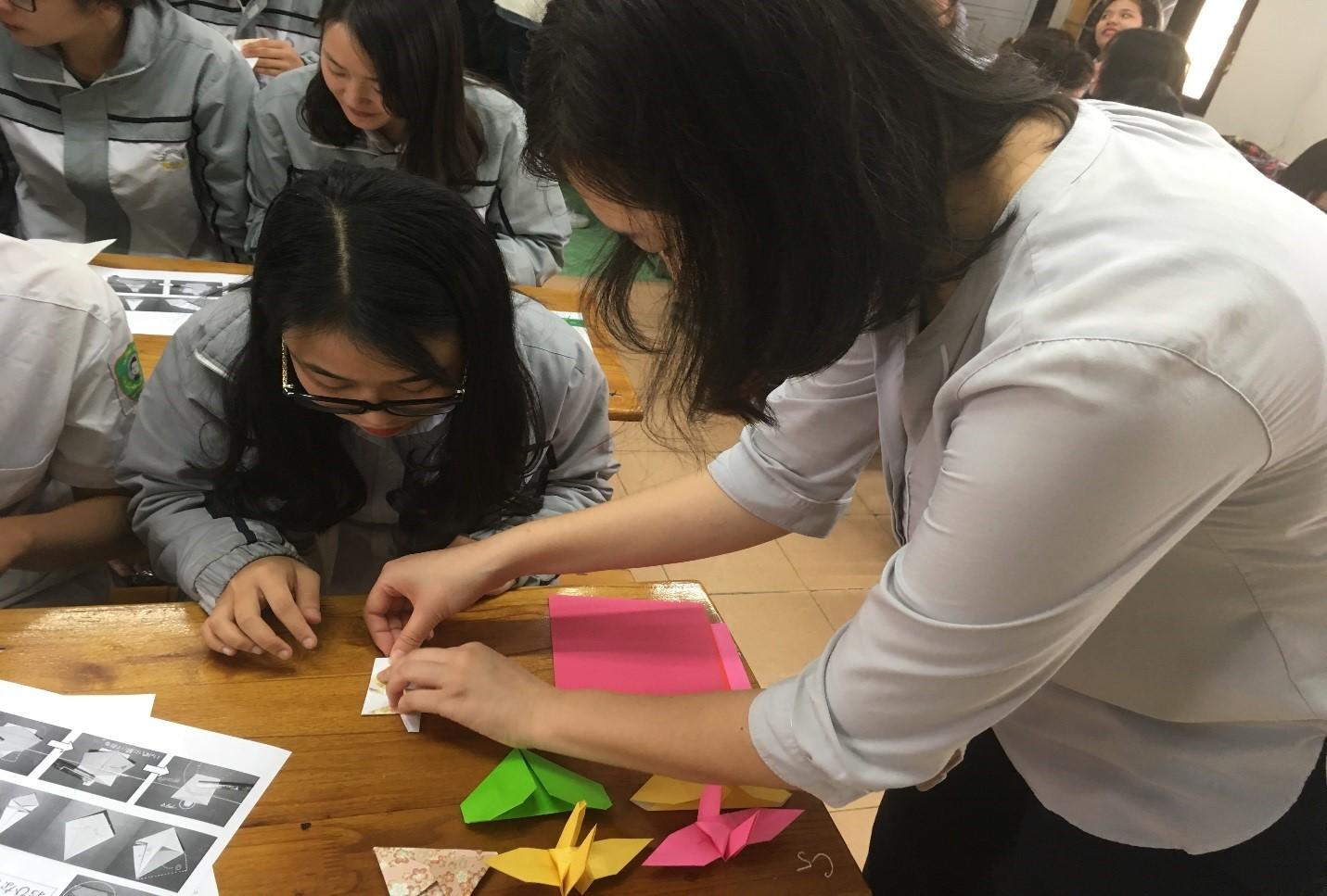 Hình ảnh: Cô giáo trực tiếp hướng dẫn học sinh gấp mô hình búp bê Nhật Bản