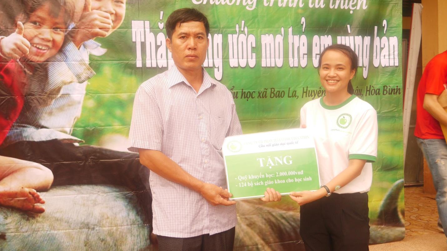 Chị Nguyễn Thị Thảo - đại diện Jellyfish Education trao tặng học bổng khuyến học và 124 bộ sách giáo khoa tới các em học sinh trường tiểu học xã Bao La